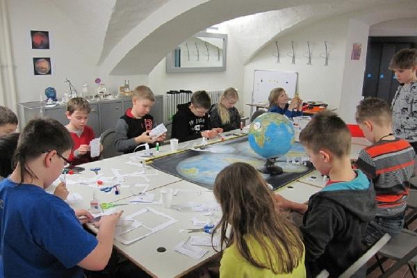 Unterrichtsprogramme für Kinder der Tartuer Sternwarte, diese sitzen rund um einen Tisch und basteln.