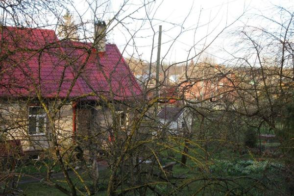 Supilinn – a district of wooden buildings with a wonderful milieu, wooden house with a red roof hidden in the trees