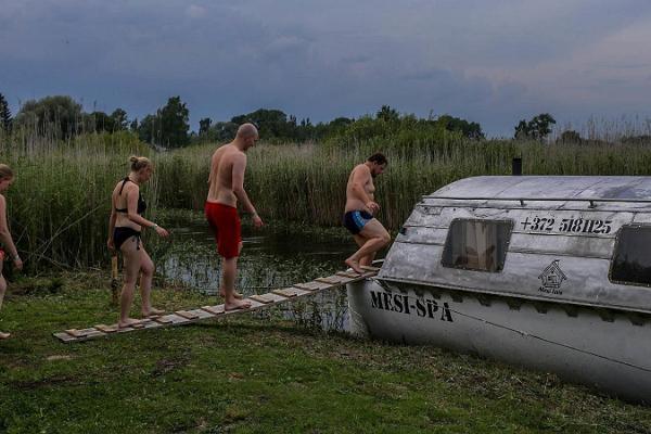 Erlebnisübernachtung im Saunaboot auf dem Peipussee, Sommerfrischler in Bekleidung zum Sonnen auf dem Weg in die Sauna