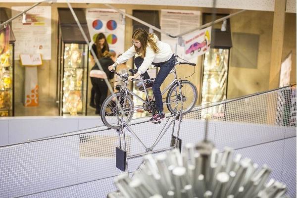 Das Wissenschaftszentrum AHHAA bietet Mutigen die Chance, mit dem Fahrrad auf einem Seil unter der Decke zu fahren.