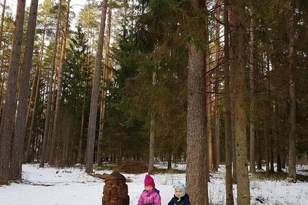 """Barnen som sitter på träet vid skulpturen. Skulpturen från estniska sagan """"Kloka mannen i fickan"""""""