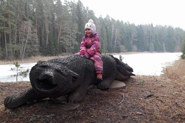Väike Väerada (Lilla Kraftled) och vargen från estnisk folklore som fiskar med svansen. En glad liten flicka sitter på träskulpturen.
