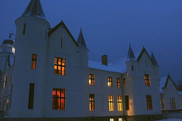 Das Herrenhaus Alatskivi nachts, während aus den Fenstern Licht dringt.