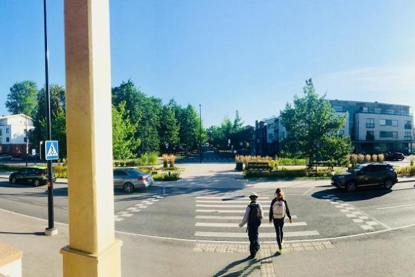 Тартуский железнодорожный вокзал, остановка такси и два пешехода, идущих по пешеходному переходу