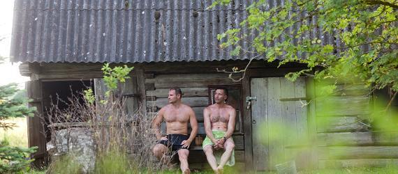 Kaksi miestä istuvat saunan edessä pyyhkeet lantiolla