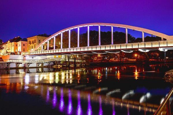 Arku tilts vasaras vakara gaismās atspoguļo apgaismojumu Emajegi upē