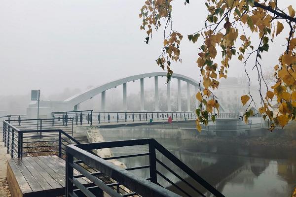Arku tilts rudenīgajā miglā un dzeltenas bērza lapas