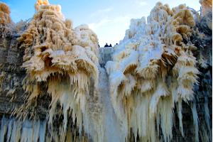 Зимние водопады на скалистом берегу с проводником