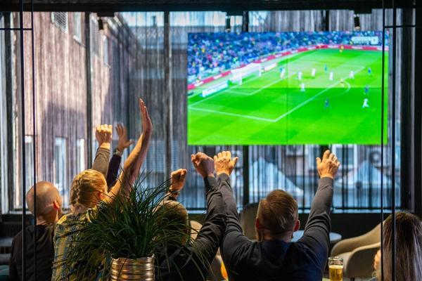 Menschen sehen erregt Fußball in der Sportbar Lucky Loore