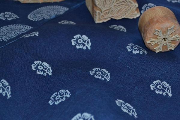 Peipusa reģiona Apmeklētāju centra audumu drukas darbnīca Sinilnik, attēlā zils audums, uz zilā auduma raksts, kas iespiests ar baltu drukas presi