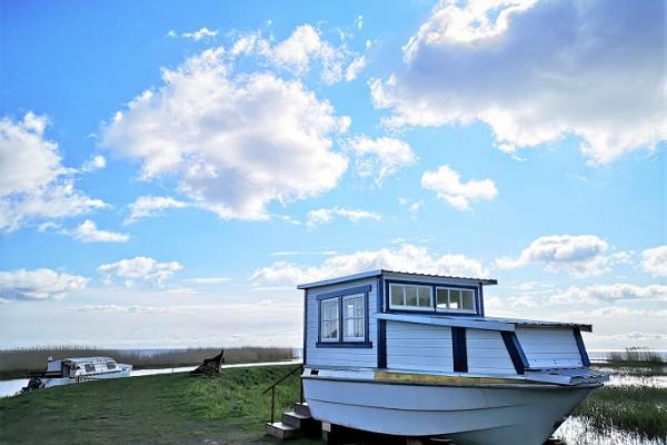 Pirts laiva un balti mākoņi gaišzilajās debesīs