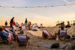 Strandstolar mellan sanddynor med utsikt över havet