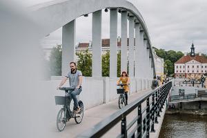 Kesäinen Kaarsild (Kaarisilta) ja Tarton pyöräpalvelun pyörillä ajelevat nuoret