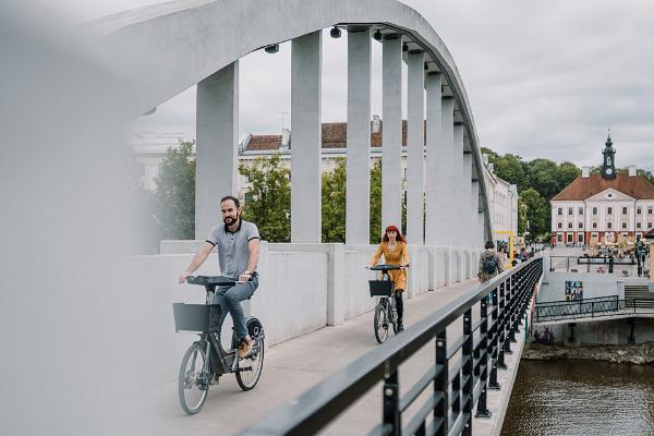 Vasarīgais Arku tilts un jaunieši ar Tartu velosipēdu nomas velosipēdiem