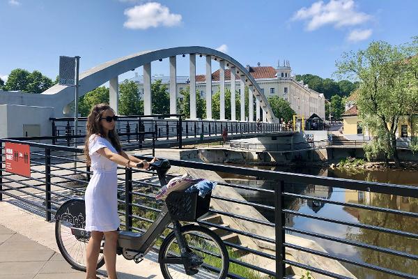 Vasarīgais Arku tilts un jauniete ar Tartu velosipēdu nomas velosipēdu