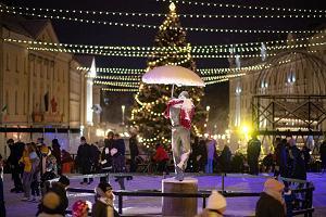 """Радостные люди, катающиеся на коньках на катке в сердце города Тарту, вокруг фонтана """"Целующиеся студенты"""""""