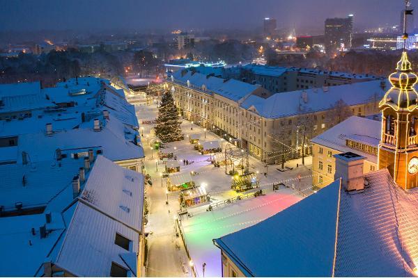 Satumaisen kaunis näkymä lumiseen joulukaupunkiin ja luistelukentälle raatihuoneen katolta