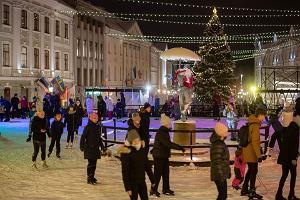 Радостные люди, катающиеся на коньках на катке в сердце города Тарту
