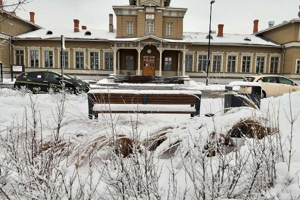 Тартуский железнодорожный вокзал снежной зимой и автобусная остановка/остановка такси, расположенная перед вокзалом