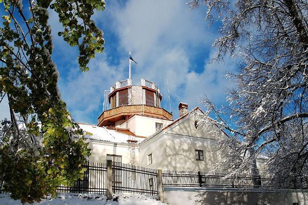 Die Tartuer Sternwarte im schneereichen Winter, am Turm weht die blauschwarzweiße Nationalfahne.