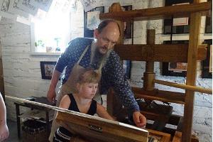 Lubokgårdens tryckpress och lubokmästaren som guidar en entusiast