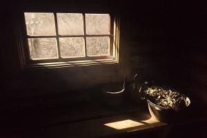 Traditsioonilise suitsusauna sisevaade, pime saun, aknast tulev valgus ja saunalise ootel saunavihad