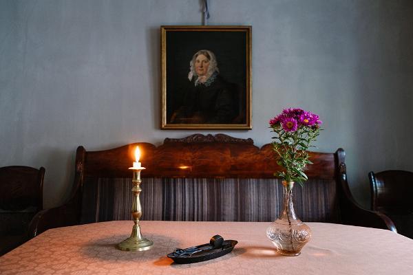 Интерьер Музея горожанина XIX века: стол, скамейки, свеча, картина