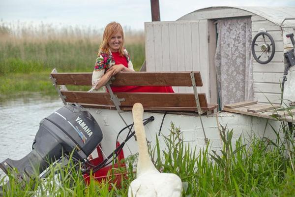 Erlebnisübernachtung im Saunaboot auf dem Peipussee –die Hausherrin der Honighütte sitzt im Saunaboot und erzählt den Schwänen etwas