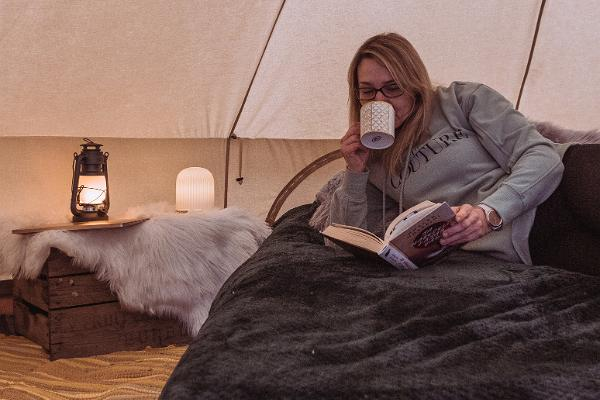 Cosy Peipsi Glamping, a woman drinking tea on the bed and reading a book