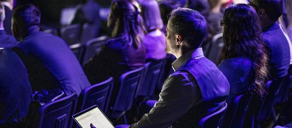 Mees rahanduskonverentsil kõnelejat kuulamas