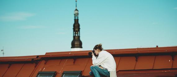 Naine fotokaameraga punasel katusel