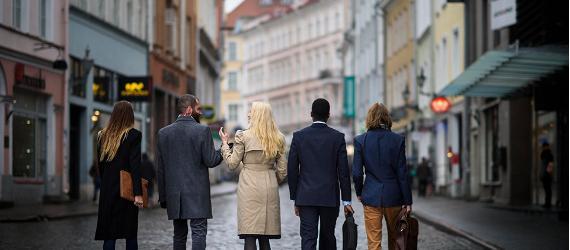 Viis inimest kõnnivad Tallinna vanalinnas, vaade neile selja tagant