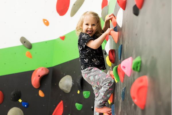 Радостная маленькая девочка наслаждается лазанием по стене для скалолазания в тартуском Министерстве скалолазания