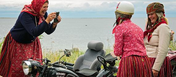 Kihnu naised mootorratta juures, üks teeb teisest kahest pilti