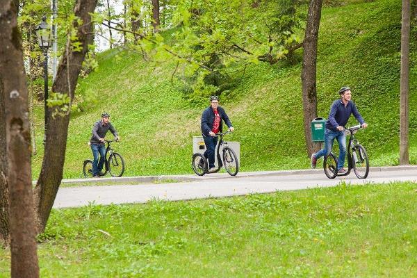 Приключение на самокатах в городе Тарту: люди на велосипедах в зеленом Тарту