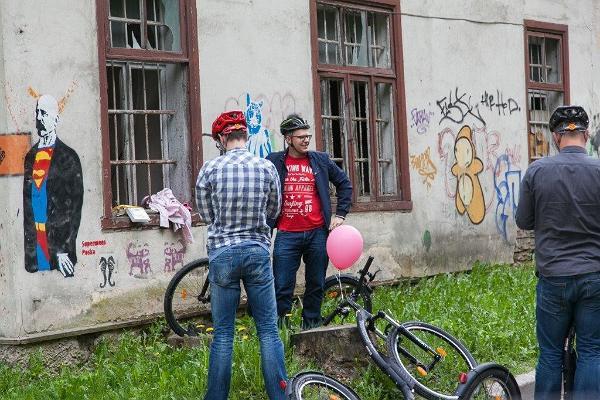 Приключение на самокатах в городе Тарту: люди на велосипедах разглядывают уличное искусство Тарту