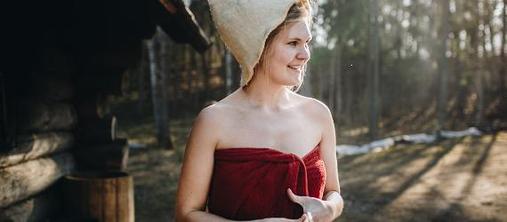 Naeratav naine suitsusauna ees saunamütsiga