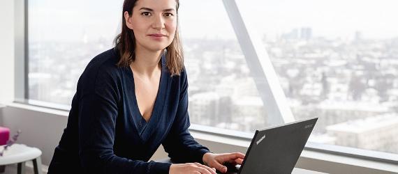 Naeratav naine istub sülearvuti taga