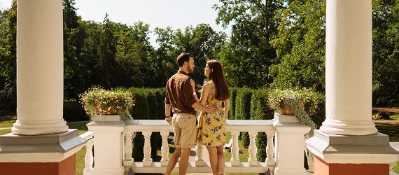 Õnnelikud noored seisavad suveriietes mõisa terrassil