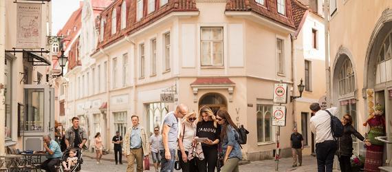 Noored turistid uurivad rahvarohkel Tallinna tänaval tahvelarvutit