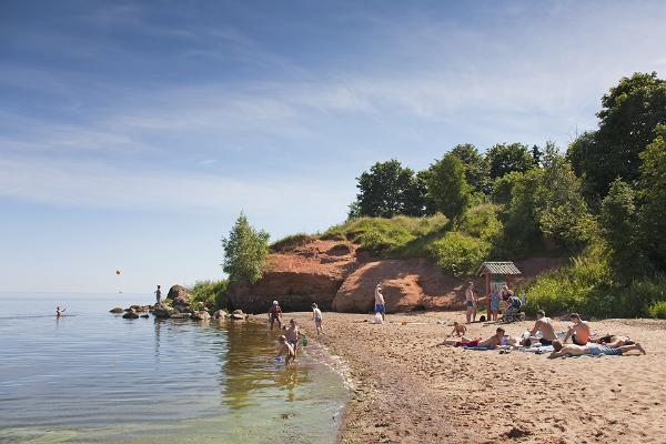 Familien genießen Strandfreuden, im Hintergrund die Klippe von Kallaste.