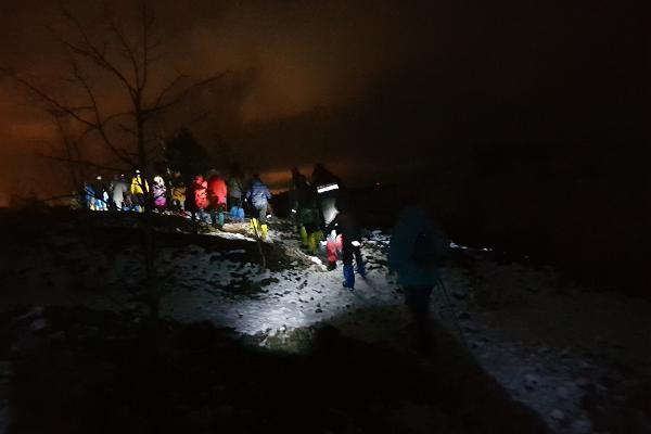 Inimesed matkamas pimedas lambivalguses mägedes