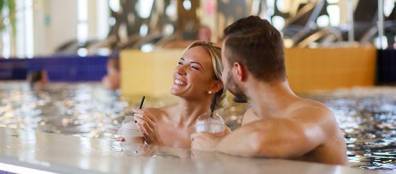Naine ja mees rõõmsalt spaa basseinis