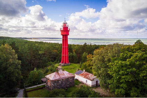 Red lighthouse in distance, sea in the background, green forest
