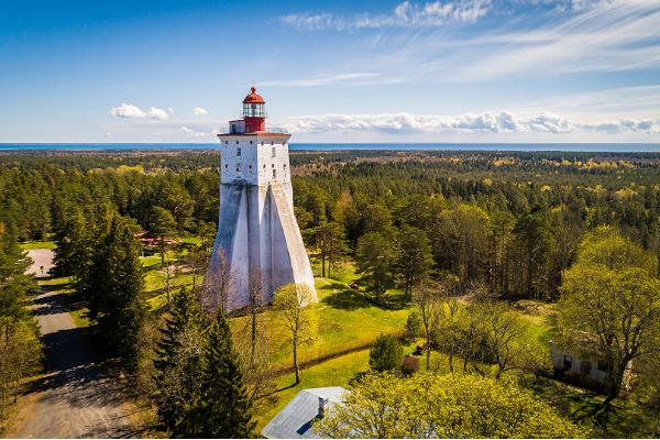 Lighthouse in distance, blue sky, green land and forest