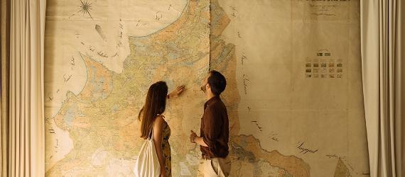Noorpaar uurimas suurt kaarti seinal