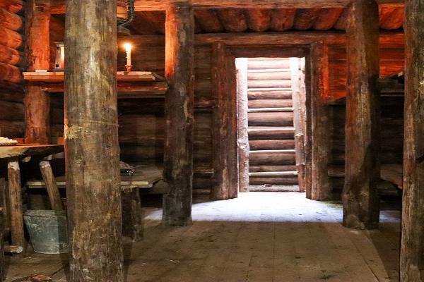 Fotoattēlā redzama bunkura galvenā telpa, kur ir sešas divstāvu gultas, plīts, izeja un ieeja tunelī.