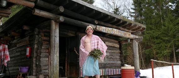 Rõõmus mees seisab suitsusauna ees